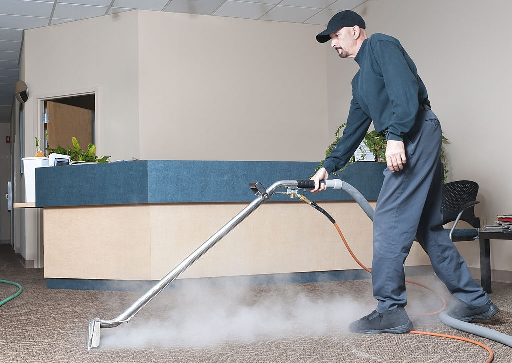 Man Steam Cleaning The Carpet Of An Office Building.